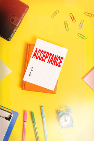 Conceptual hand writing showing Acceptance. Concept meaning when you agree to take something officially or act of taking it Pile of empty papers with copy space on the table