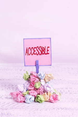 Text sign showing Accessible. Business photo text defined as something you can get to use or obtain or reach Reminder pile colored crumpled paper clothespin reminder white wooden space