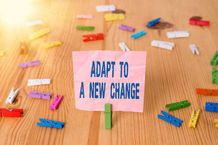 Conceptual hand writing showing Adapt To A New Change. Concept meaning Get used to latest Mindset and Behavior Innovation Colored crumpled papers wooden floor background clothespin