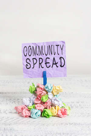 Writing note showing Community Spread. Business concept for dissemination of a highlycontagious disease within the local area Reminder pile colored crumpled paper clothespin wooden space