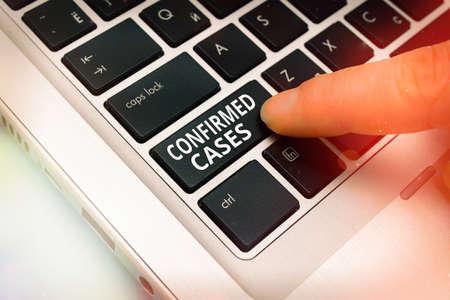 Word writing text Confirmed Cases. Business photo showcasing set of circumstances or conditions requiring action Pc keyboard key with pointing finger above background copy space