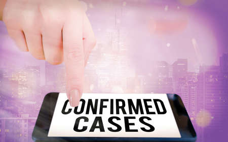 Writing note showing Confirmed Cases. Business concept for set of circumstances or conditions requiring action Modern gadgets white screen under colorful bokeh background