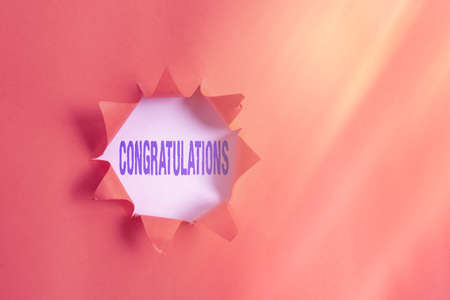 Text sign showing Congratulations. Business photo text a special occasion that expressing gratitude or good wishes Rolled ripped torn cardboard placed above a wooden classic table backdrop