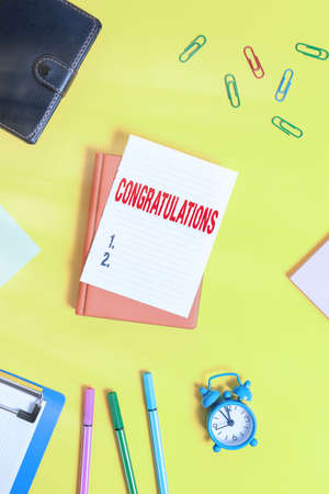 Conceptual hand writing showing Congratulations. Concept meaning a special occasion that expressing gratitude or good wishes Pile of empty papers with copy space on the table
