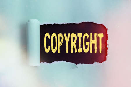 Word writing text Copyright. Business photo showcasing exclusive legal right to print write perform film record literary Rolled ripped torn cardboard placed above a wooden classic table backdrop