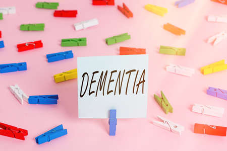 Word writing text Dementia. Business photo showcasing the general word for diseases and disorders with a loss in memory Colored clothespin papers empty reminder pink floor background office pin Zdjęcie Seryjne
