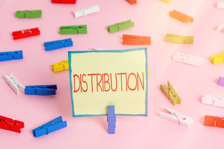Text sign showing Distribution. Business photo text the behavior of several recipients sending something out Colored clothespin papers empty reminder pink floor background office pin Фото со стока