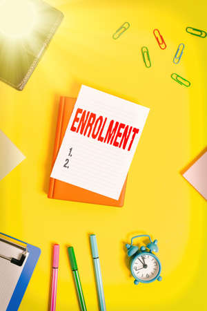 Conceptual hand writing showing Enrolment. Concept meaning the act of putting yourself on the official course members list Pile of empty papers with copy space on the table