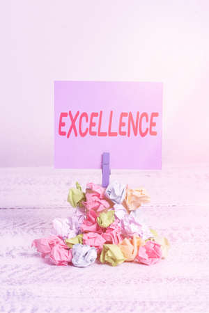 Word writing text Excellence. Business photo showcasing standard of performance of simply being the best at something Reminder pile colored crumpled paper clothespin reminder white wooden space