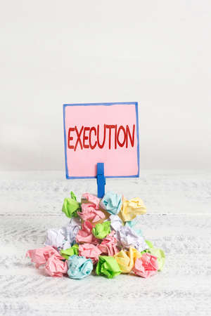 Text sign showing Execution. Business photo text it executes or imposes a program order or course of action Reminder pile colored crumpled paper clothespin reminder white wooden space