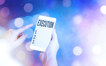Conceptual hand writing showing Execution. Concept meaning it executes or imposes a program order or course of action Modern gadgets white screen under colorful bokeh background
