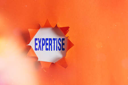 Text sign showing Expertise. Business photo text specific competences of skills gained through training practice Rolled ripped torn cardboard placed above a wooden classic table backdrop