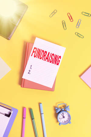 Conceptual hand writing showing Fundraising. Concept meaning applying for financial aid for a charity, cause or undertaking Pile of empty papers with copy space on the table Фото со стока