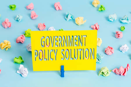 Text sign showing Government Policy Solution. Business photo text designed game plan created in response to emergency disaster Colored crumpled papers empty reminder blue floor background clothespin