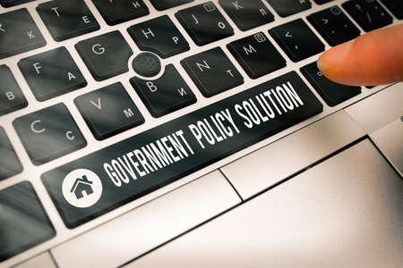 Writing note showing Government Policy Solution. Business concept for designed game plan created in response to emergency disaster Pc keyboard key with pointing finger above background copy space