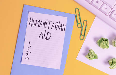 Word writing text Humanitarian Aid. Business photo showcasing immediate assistance provided after natural and manmade disaster Flat lay above empty copy space white paper with paper clips on the table Stock fotó