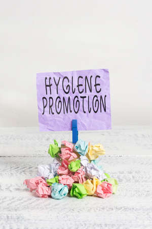 Writing note showing Hygiene Promotion. Business concept for systematic program to prevent related disease with sanitation Reminder pile colored crumpled paper clothespin wooden space
