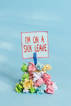 Handwriting text Im On A Sick Leave. Conceptual photo paid time off from work to address their health issue Reminder pile colored crumpled paper clothespin reminder blue background