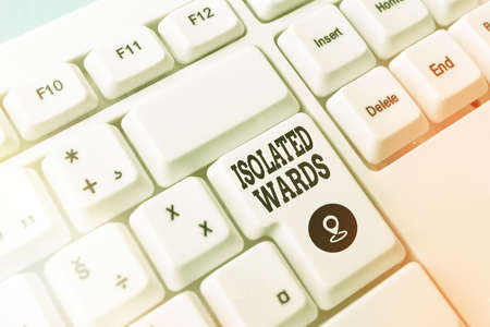 Text sign showing Isolated Wards. Business photo showcasing far away from places or showing and having minimal contact Pc keyboard key with empty note paper above background copy space