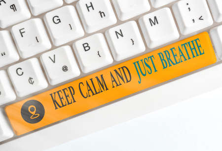 Conceptual hand writing showing Keep Calm And Just Breathe. Concept meaning Take a break to overcome everyday difficulties Colored keyboard key with accessories arranged on copy space Standard-Bild