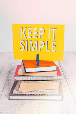 Conceptual hand writing showing Keep It Simple. Concept meaning ask something easy understand not go into too much detail pile stacked books notebook pin color reminder white wooden
