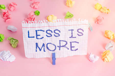 Conceptual hand writing showing Less Is More. Concept meaning used to express a minimalist approach is more effective. Colored crumpled papers empty reminder pink floor clothespin
