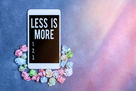 Text sign showing Less Is More. Business photo showcasing used to express a minimalist approach is more effective. Paper accesories with digital smartphone arranged on different background Banco de Imagens