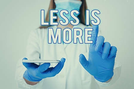 Conceptual hand writing showing Less Is More. Concept meaning used to express a minimalist approach is more effective. Laboratory technician featuring paper accessories smartphone Banco de Imagens