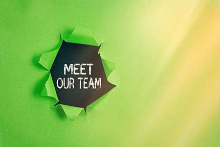 Writing note showing Meet Our Team. Business concept for introducing another an individual to your teammates in the company Rolled ripped torn cardboard above a wooden classic table