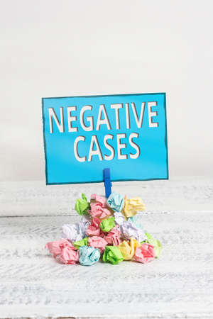 Text sign showing Negative Cases. Business photo showcasing circumstances or conditions that are confurmed to be false Reminder pile colored crumpled paper clothespin reminder white wooden space