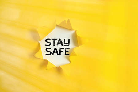 Handwriting text Stay Safe. Conceptual photo secure from threat of danger, harm or place to keep articles Rolled ripped torn cardboard placed above a wooden classic table backdrop