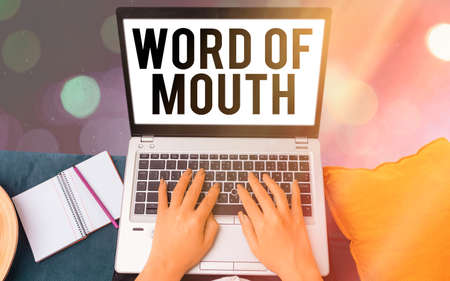 Conceptual hand writing showing Word Of Mouth. Concept meaning information that is transmitted without being written down Modern gadgets white screen under colorful bokeh background 免版税图像
