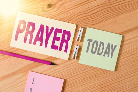 Conceptual hand writing showing Prayer. Concept meaning solemn request for help or expression of thanks addressed to God Colored crumpled papers wooden floor background clothespin Banco de Imagens