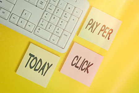 Handwriting text Pay Per Click. Conceptual photo internet marketing in which payment is based on clickthrough Colored empty papers with copy space on the yellow background table with pc keyboard
