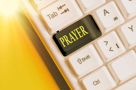 Conceptual hand writing showing Prayer. Concept meaning solemn request for help or expression of thanks addressed to God Colored keyboard key with accessories arranged on copy space Stock Photo