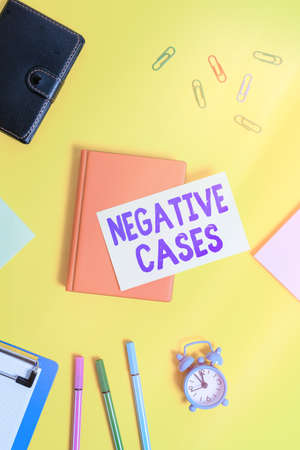 Text sign showing Negative Cases. Business photo text circumstances or conditions that are confurmed to be false Flat lay above table with copy space paper clips clock and pencils Foto de archivo