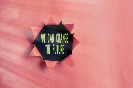 Conceptual hand writing showing We Can Change The Future. Concept meaning Make actions to achieve different results Rolled ripped torn cardboard above a wooden classic table
