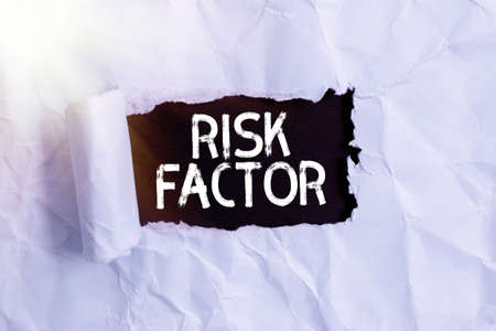Handwriting text Risk Factor. Conceptual photo Characteristic that may increase the percentage of acquiring a disease Rolled ripped torn cardboard placed above a wooden classic table backdrop Reklamní fotografie