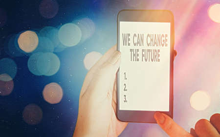 Conceptual hand writing showing We Can Change The Future. Concept meaning Make actions to achieve different results Modern gadgets white screen under colorful bokeh background