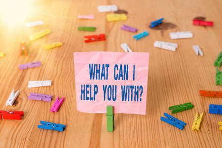 Conceptual hand writing showing What Can I Help You With Question. Concept meaning to make it possible for someone to do Colored crumpled papers wooden floor background clothespin