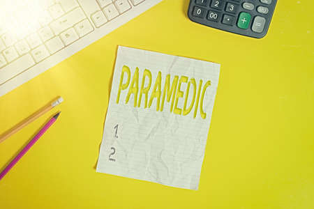 Writing note showing Paramedic. Business concept for a health worker having an expertise in emergency medical work Copy space on notebook above yellow background with keyboard on table