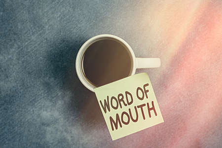 Conceptual hand writing showing Word Of Mouth. Concept meaning information that is transmitted without being written down Paper accessories with smartphone on different background