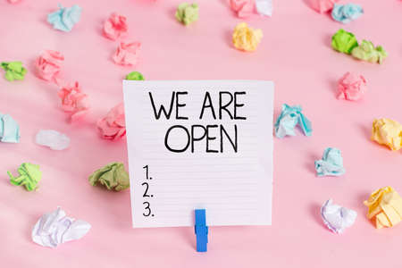 Conceptual hand writing showing We Are Open. Concept meaning no enclosing or confining barrier, accessible on all sides Colored crumpled papers empty reminder pink floor clothespin