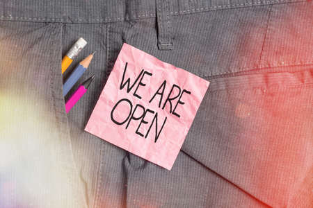 Text sign showing We Are Open. Business photo text no enclosing or confining barrier, accessible on all sides Writing equipment and pink note paper inside pocket of man work trousers