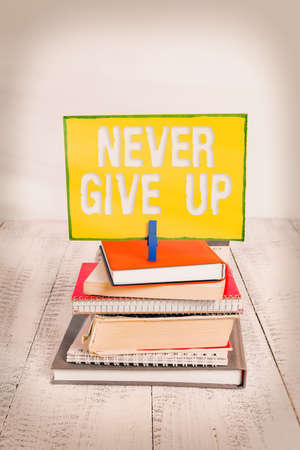 Handwriting text Never Give Up. Conceptual photo be persistent to keep on trying to improve the condition pile stacked books notebook pin clothespin colored reminder white wooden Stock Photo