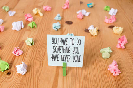 Handwriting text You Have To Do Something You Have Never Done. Conceptual photo to change your mindset Colored crumpled papers empty reminder wooden floor background clothespin