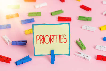 Text sign showing Priorities. Business photo text more important is the fact or state of being viewed or handled Colored clothespin papers empty reminder pink floor background office pin 写真素材