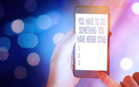 Conceptual hand writing showing You Have To Do Something You Have Never Done. Concept meaning to change your mindset Modern gadgets white screen under colorful bokeh background