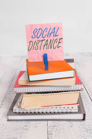 Word writing text Social Distance. Business photo showcasing maintaining a high interval physical distance for public health safety pile stacked books notebook pin clothespin colored reminder white wooden Stock Photo