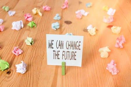 Handwriting text We Can Change The Future. Conceptual photo Make actions to achieve different results Colored crumpled papers empty reminder wooden floor background clothespin